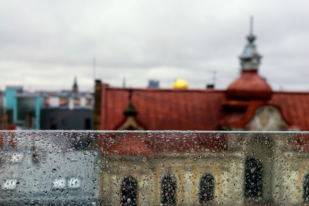 glass partition: The roofs of the city from the top of the glass partition with raindrops and the horizon. Riga, Latvia