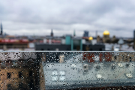 Roofs and spiers of the city behind a glass partition in the rain. Latvia, Riga. Baltic state