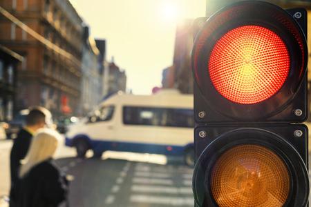 Пара пересекая улицу на перекрестке со светофором, на закате, с подсветкой