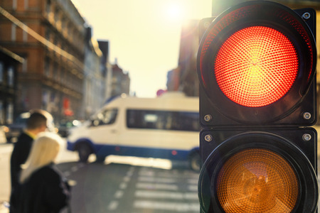 Couple crossing the street at an intersection with traffic lights at sunset, backlit Stock Photo