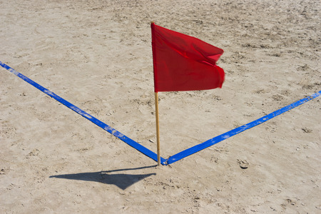 Red flag and blue corner on the golden sand beach Stock Photo