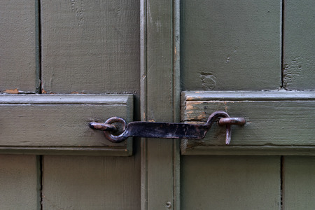Forged steel hook closes the two halves of a green door Stock Photo