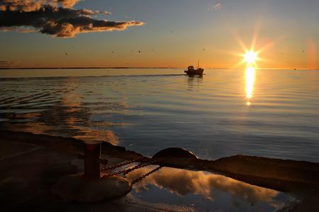 Рыбацкая лодка в Балтийское море с пирса в порту на рассвете солнца на горизонте