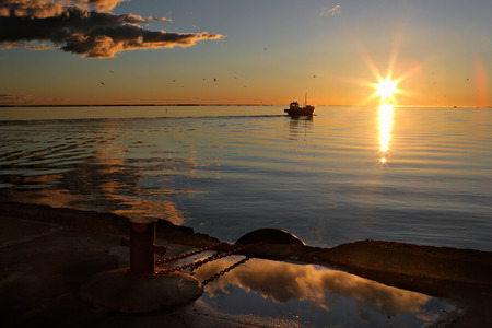 beautiful sunset: Fishing boat out into the Baltic Sea from the pier of the port at sunrise of the sun at the horizon Stock Photo