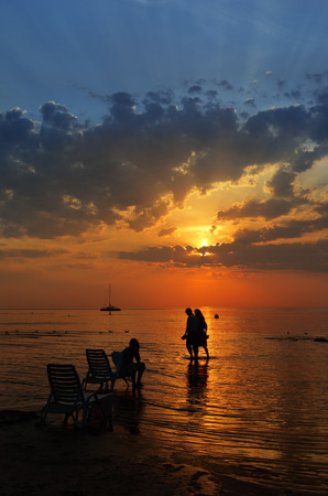 baltic people: Silhouettes of people and a yacht on the Baltic Sea in the summer during sunset Stock Photo