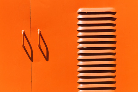 ventilate: Iron orange colored door handles and shadows with ventilation slots Stock Photo