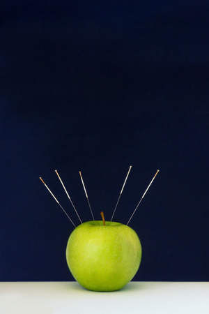 Acupuncture needles stuck into a green apple as a symbol of precision treatment Фото со стока