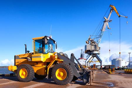 Желтый погрузчик и кран на разгрузка и погрузка грузов в порту на фоне голубого неба
