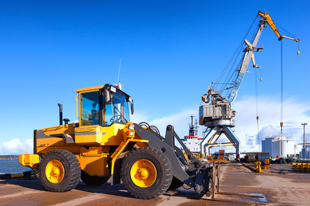 Yellow forklift and crane at unloading and loading cargo at the port on a background of blue sky Фото со стока