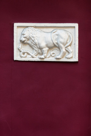 thumbnail: Thumbnail relief of a lion and a snake on the red facade of an old building Stock Photo