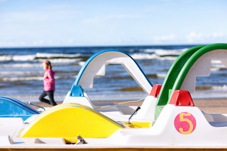 Girl runs on a background of blue and green water rides on a sunny autumn Baltic Sea beach Stock Photo