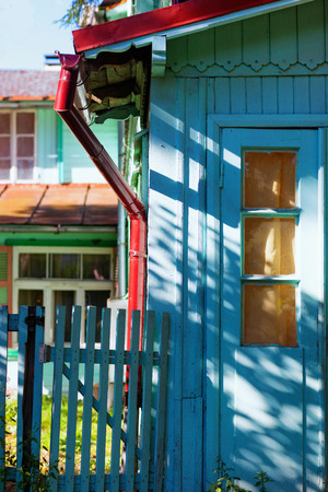 Summer brightly colored house with a gate on a sunny summer day