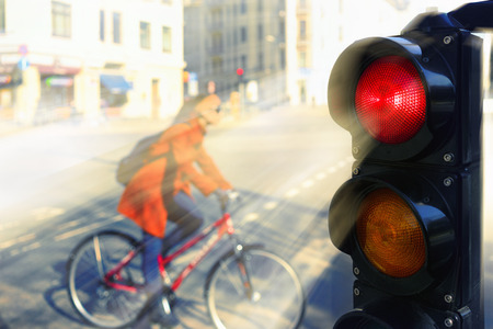latvia girls: Girl in a red coat on a bicycle at the intersection of the city for a red traffic light in spring day Stock Photo