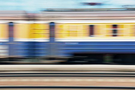 Passenger train passing quickly past the station at a speed on a sunny day Stock Photo