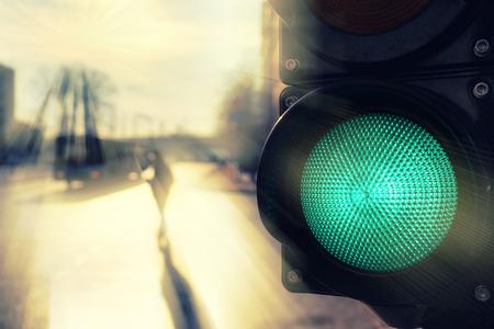 Пешеход переходил дорогу на солнце на светофоре с зеленым весной сигнала Фото со стока