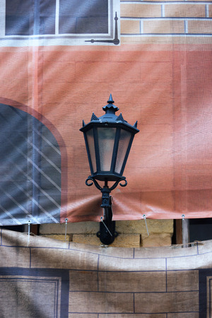 Street lamp on a fake painted facade of the house to be repaired
