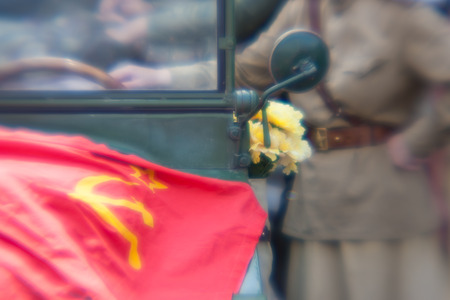 soviet flag: A woman in military uniform at the Soviet flag with hammer and sickle on the vintage jeep with flowers. Blurry Stock Photo