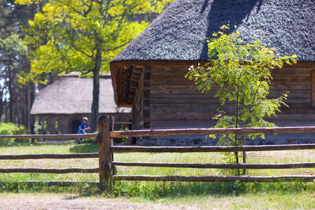 The boy runs into old wooden house with a thatched roof outside the fence Stock Photo