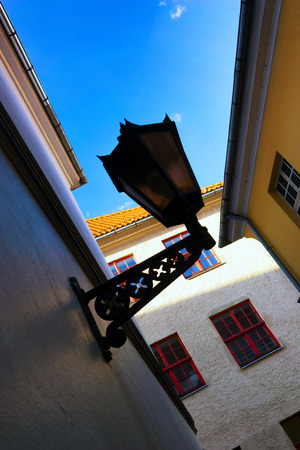 Street lamp between colored walls of houses against the blue sky in Riga Stock Photo
