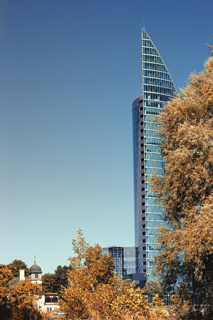 compared: The modern building of glass and concrete on a background of sky and trees in autumn compared to conventional buildings