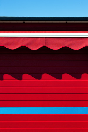 awnings: Red wall with striped awnings curves and shadow on a background of blue sky