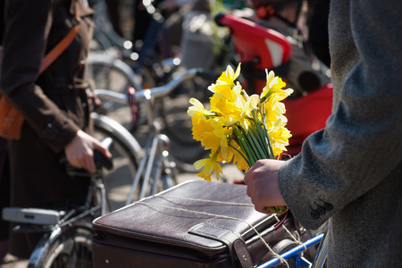 latvia girls: Yellow daffodils in the hand of a man with a bicycle and a suitcase at a meeting with a girl Stock Photo