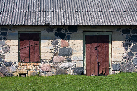 slate roof: Estonia. Saarema. Wall of the rural house of stone with closed lock on the door and the window at the green lawn under a slate roof Stock Photo