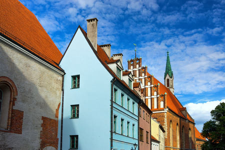 tall chimney: Latvia. The original medieval house with a tall chimney and a church with a green spire in Riga Stock Photo