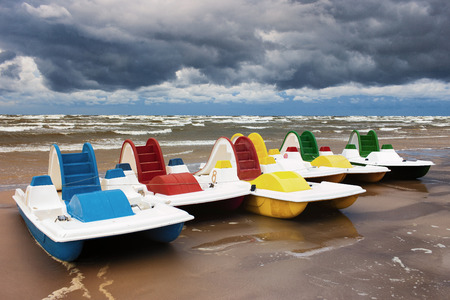 pedals: Latvia. Jurmala. Pleasure boat with pedals connected to the castle on the sandy beach in a storm on the sea with storm clouds