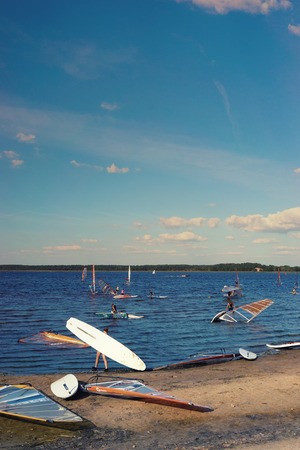 sailboard: Latvia. Windsurfing on the background of clear blue sky with clouds preparing to swim near the shore of the lake on a sunny day