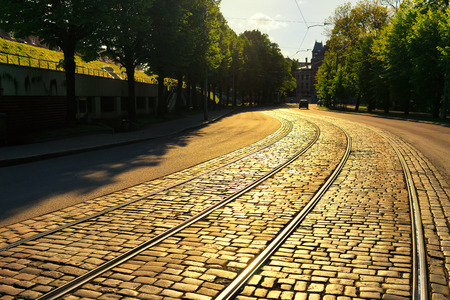 Latvia, Riga. Evening sunlight on a bend of the street with the tram rails cobblestones near the park