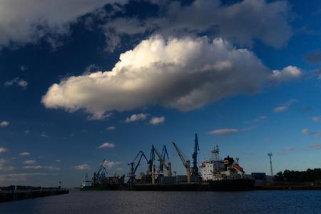 Baltic, Latvia. Beautiful big cloud over the cargo sea port with cranes in Riga Stock Photo