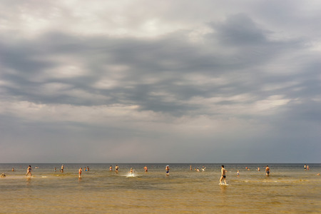 baltic people: Latvia. Vacationers people in bathing suits walking in the summer at low tide the water of the Baltic Sea from the sandy beach in heavy clouds Stock Photo