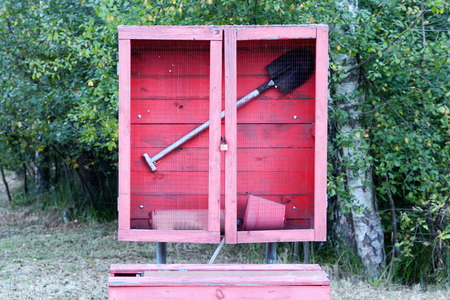 fire shield: Red fire shield with a shovel, a bucket and a fire extinguisher on a background of leafy green forest Stock Photo