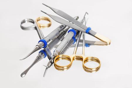dentista: Conjunto de diversas herramientas de acero y oro para la pr�ctica de un dentista en un fondo blanco con la reflexi�n