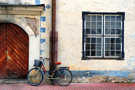 Latvia, Riga. Bicycle standing on a red stone blocks at the wooden gate in an old house with a square window on the old yellow wall.