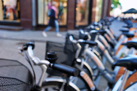 misses: She misses the parking city bikes and shop windows on a summer day. Blurry