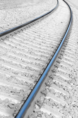 Bending rails and concrete sleepers with white stones on the railway line turn into perspective Stock Photo
