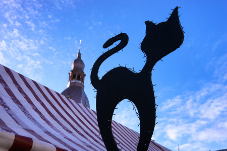 spire: Silhouette of a black cat with light bulbs on the Christmas fair in the background the spire of the Dome Cathedral in Riga