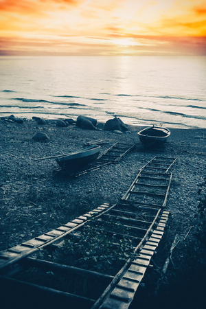 Fishing boats on the beach with stones and wooden ladder at sunset. Baltic Sea