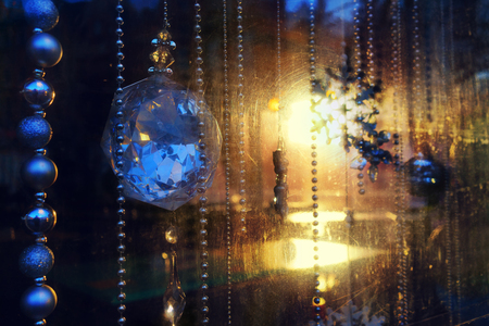 christmas beads: Christmas beads and glass balls through the scratched glass windows with a yellow sun and glare