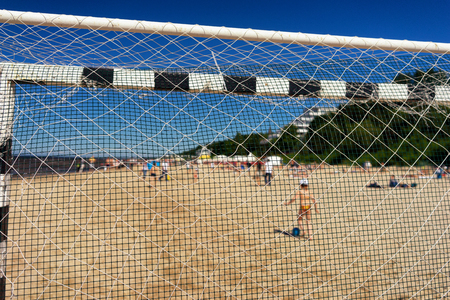 football play: The boy with a ball on the sandy beach of the Baltic Sea with holiday travelers through the mesh football goal on a summer sunny day. Blurry. Latvia
