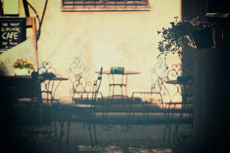 taverna: Outdoor cafe with beautiful flowers and vintage chairs in a stylish courtyard of the house. Latvia, Riga Stock Photo