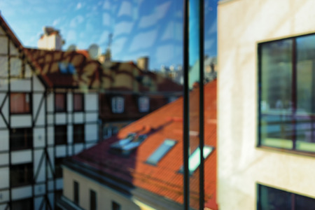 upper floor: City landscape on the roofs of Riga with the traditional pattern of the walls of the upper floor windows with reflection. Blurry