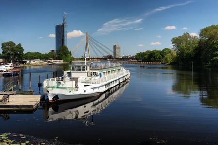 pleasure ship: Pleasure river ship against the background of a suspension bridge and the skyline of Riga in spring. Latvia