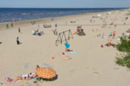 jurmala: Top view of a yellow sandy beach on the Baltic Sea with people sunbathing on a sunny day. Blurry Stock Photo