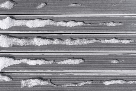 striped lines: Snow melts on the boards in striped lines on the terrace of the house in spring Stock Photo