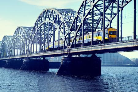 trait: Blue with yellow electric train rides on the railway bridge over the river Daugava in Riga Stock Photo