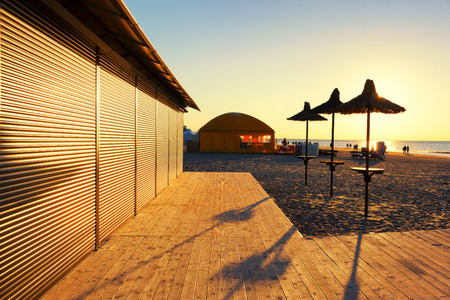 vacationers: Wooden terrace with beach umbrellas and a cafe in the sunlight and promising lines at sunset with vacationers people
