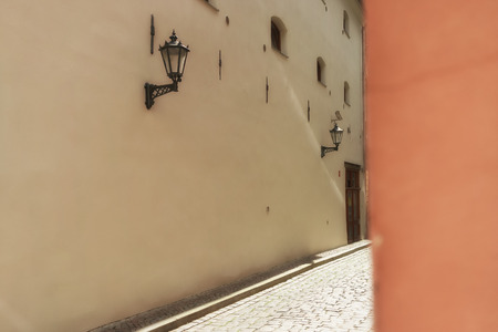 corner of house: Wall with street lamp on the wall of a building on the street with stones and orange corner house in the old city of Riga